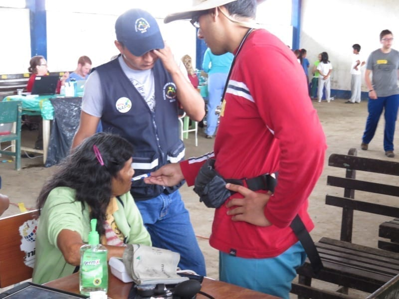 Medical student taking temperatures, translated by EC social worker from Spanish into Quichua in the Amazon Jungle