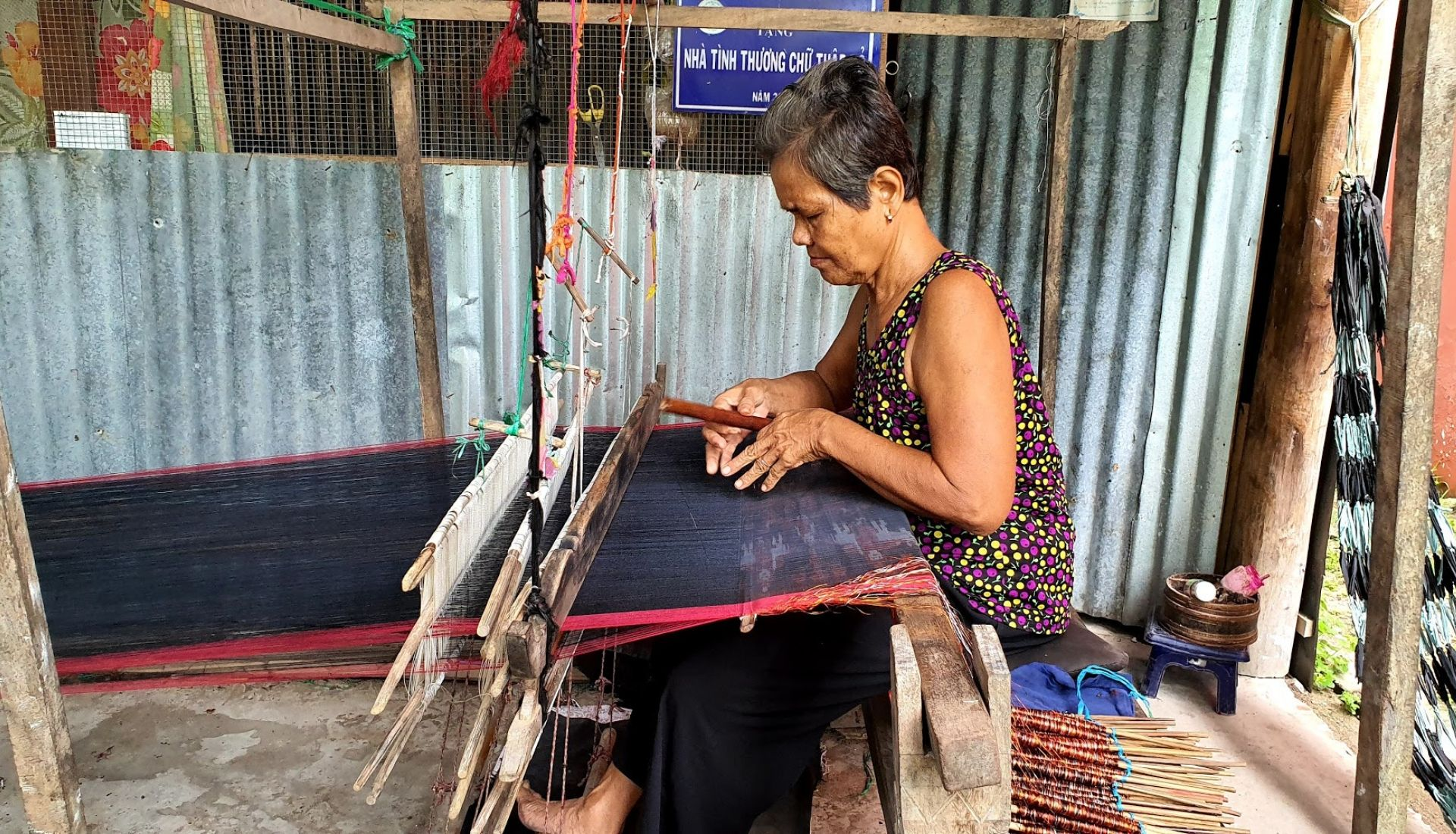Khmer woman weaving traditional shawls